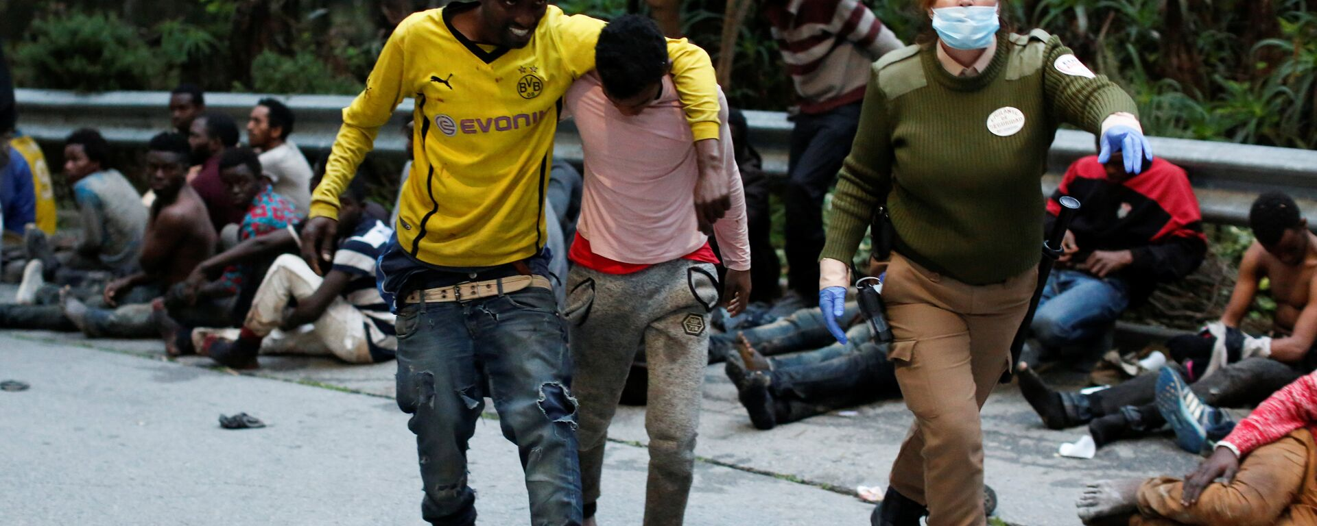 African migrants help each other as they arrive at the CETI, the short-stay immigrant centre, after crossing the border from Morocco to Spain's North African enclave of Ceuta, Spain, February 17, 2017 - Sputnik Italia, 1920, 20.05.2021