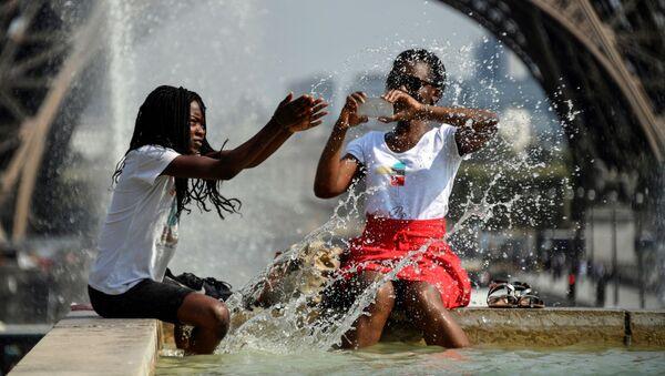 Due ragazze cercato sollievo dal caldo in una fontana di fronte alla Tour Eiffel di Parigi - Sputnik Italia