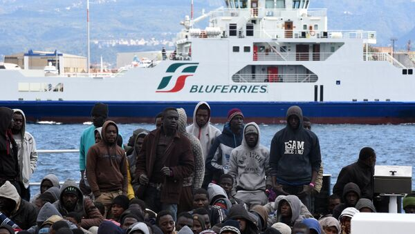Migrants and refugees wait to disembark in the port of Messina following a rescue operation at sea by the Italian Coast Guard ship Diciotti on March 17, 2016 in Sicily. - Sputnik Italia