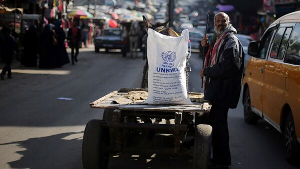 A Palestinian man stands next to a cart carrying a flour sack distributed by the United Nations Relief and Works Agency (UNRWA) in Khan Younis refugee camp in the southern Gaza Strip January 3, 2018 - Sputnik Italia