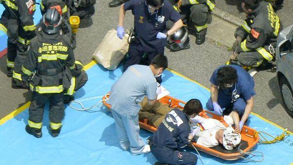 Un passeggero riceve assistenza medica da parte dei soccorritori dopo la fermata di emergenza del treno proiettile Shinkansen, il 30 giugno 2015. - Sputnik Italia