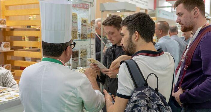 Uno chef spiega i segreti della pasta a questi giovani visitatori del padiglione italiano di World Food Expo