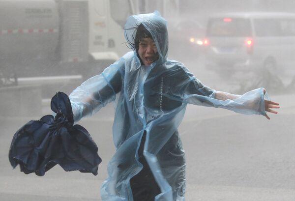 Una donna nella pioggia causata dal typhoon Mankhut in Cina - Sputnik Italia