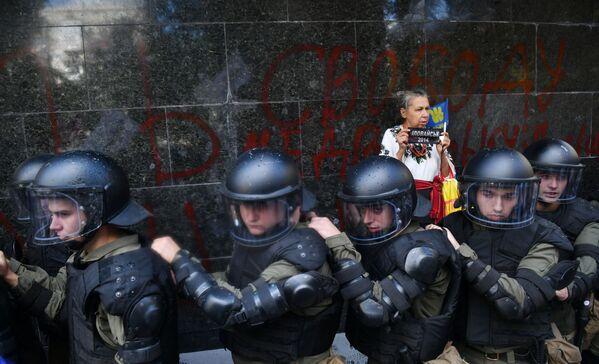 Una donna sta dietro i poliziotti alla sede della procura generale dell'Ucraina - Sputnik Italia