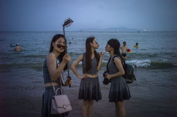 Ragazze cinesi si fotografano sulla spiaggia della città di Xindao - Sputnik Italia