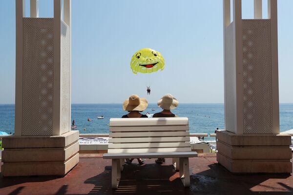 Spettatori osservano paracadutista ascensionale a Nizza, Francia - Sputnik Italia