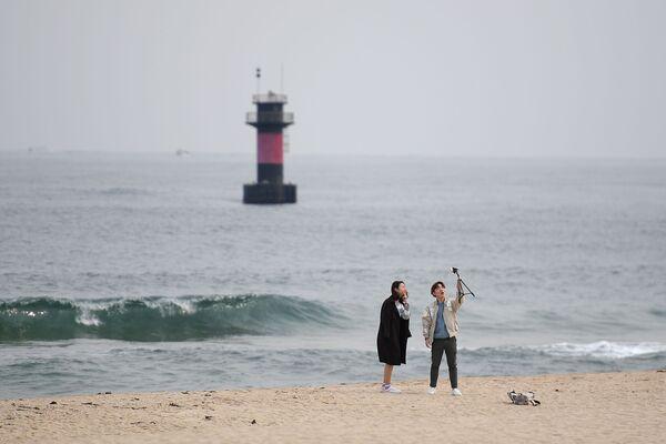 Giovani si scattano foto sulla spiaggia di Gyeongpo nella città di Kannyn, Repubblica di Corea - Sputnik Italia
