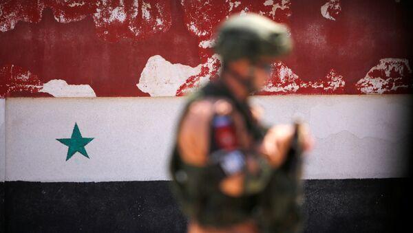 Un soldato russo sta di fronte alla bandiera nazionale siriana - Sputnik Italia