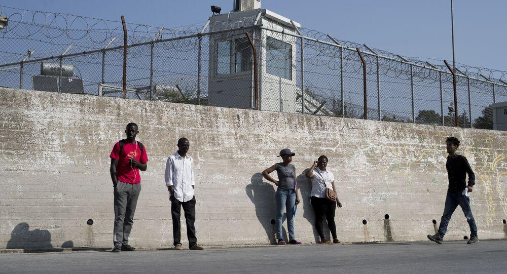 Migranti stanno fuori le mura del campo per i rifugiati di Moria nell'isola di Lesbo, Grecia.