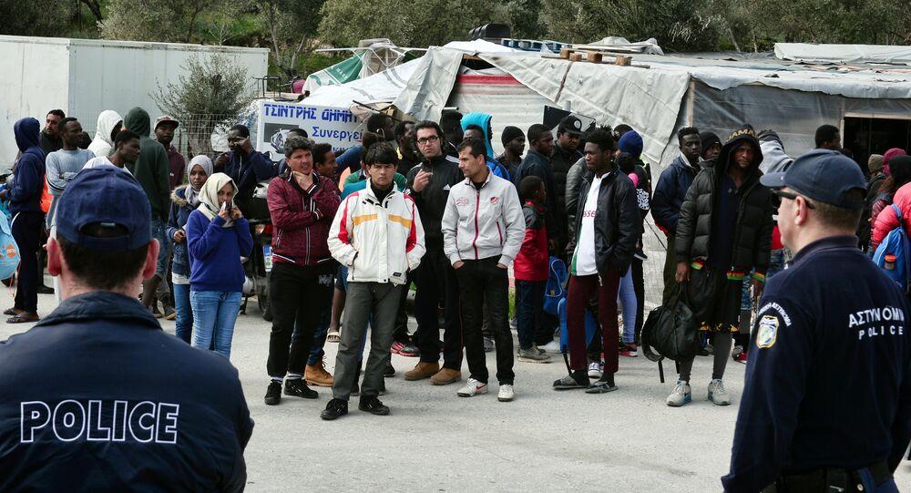 Poliziotti guardano migranti al campo per i rifugiati di Moria sull'isola di Lesbo, Grecia