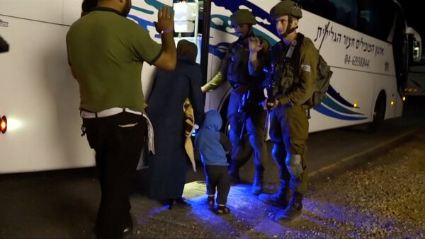People walk past Israeli soldiers as they board a bus during the Syria Civil Defence, also known as the White Helmets, extraction from the Golan Heights, Israel in this still image taken from video, provided by the Israeli Army July 22, 2018 - Sputnik Italia