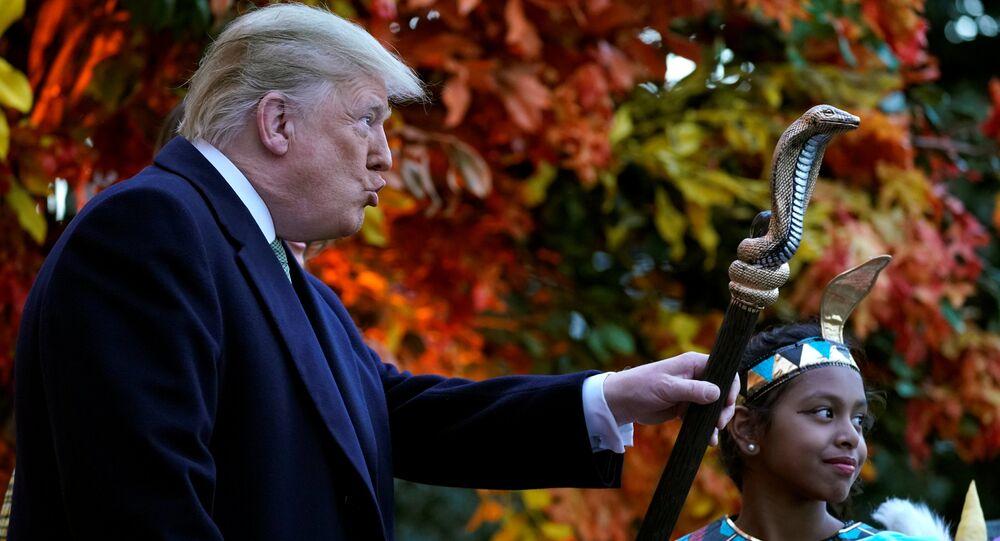 Il presidente statunitense Donald Trump sta con un bambino vestito da faraone per l'Halloween.