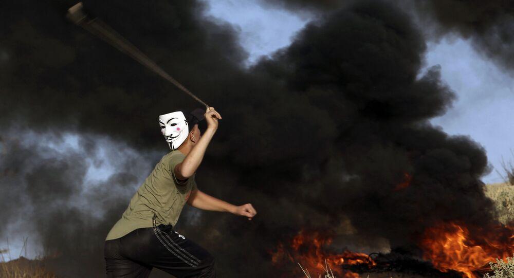 Un manifestante lancia un sasso all'esercito israeliano alla frontiera tra la striscia di Gaza ed Israele.