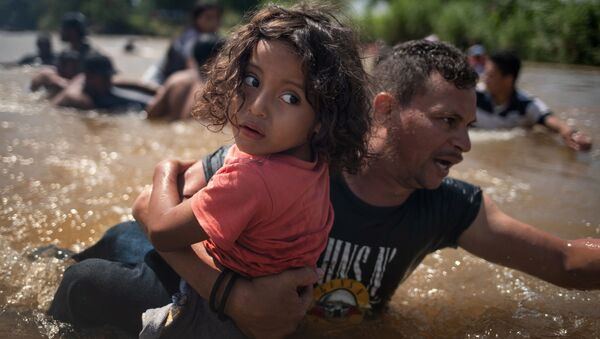 Migranti dall'Honduras attraversano a piedi il fiume Suchiate al confine con il Messico, durante il loro viaggio verso gli USA. - Sputnik Italia