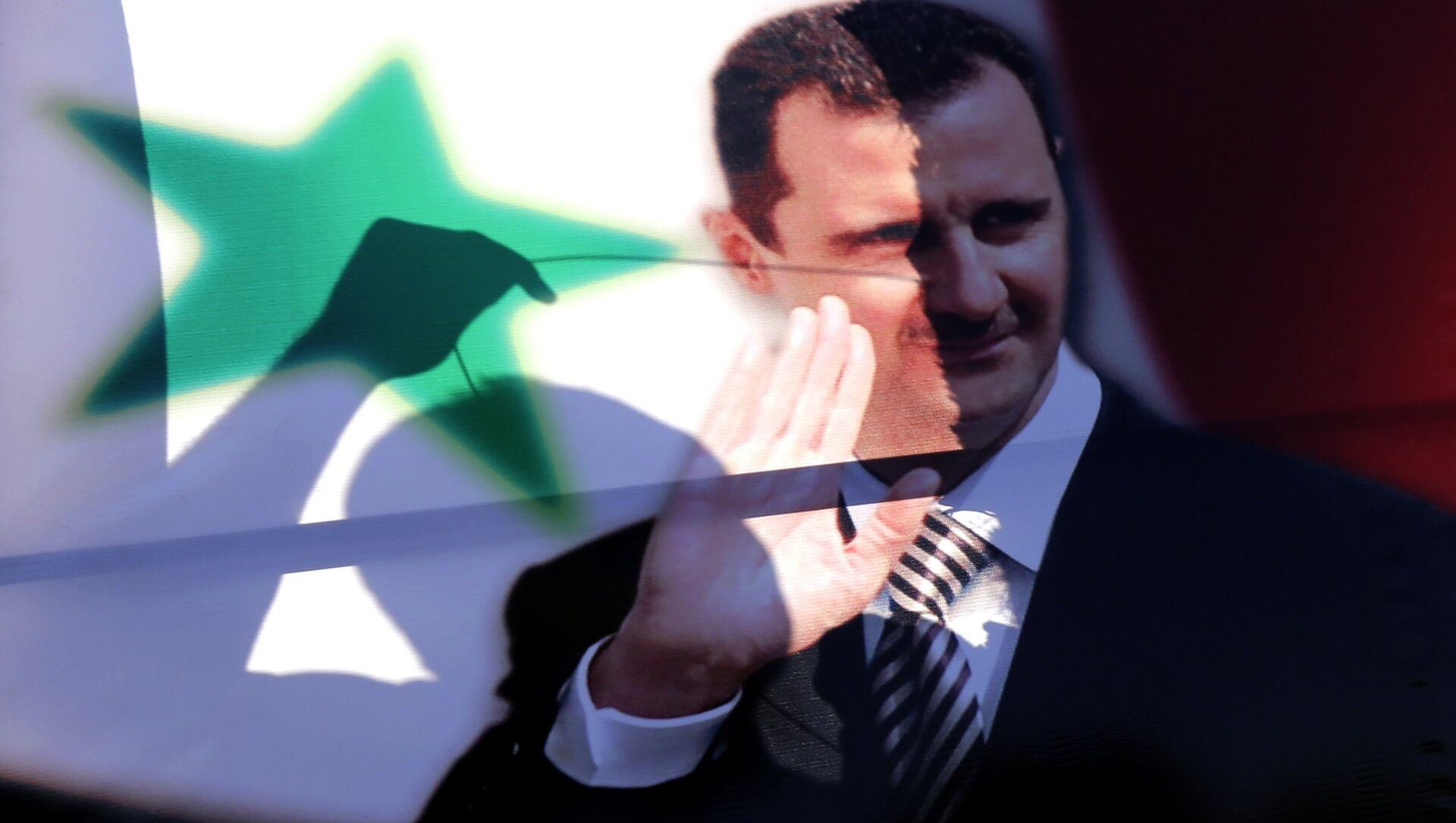 La siluetta di un siriano vista tra il ritratto del presidente siriano Bashar al-Assad - Sputnik Italia, 1920, 11.02.2021