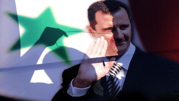 La siluetta di un siriano vista tra il ritratto del presidente siriano Bashar al-Assad - Sputnik Italia