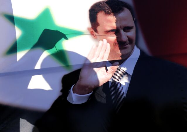 La siluetta di un siriano vista tra il ritratto del presidente siriano Bashar al-Assad