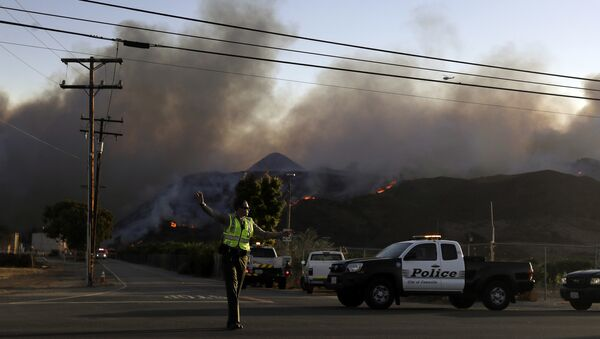 A police officer mans a checkpoint in front of an advancing wildfire Thursday, Nov. 8, 2018, near Newbury Park, Calif. The Ventura County Fire Department has also ordered evacuation of some communities in the path of the fire, which erupted a few miles from the site of Wednesday night's deadly mass shooting at a Thousand Oaks bar. - Sputnik Italia