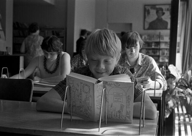Un ragazzo legge un libro in biblioteca
