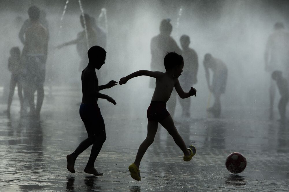 Ragazzi giocano a calcio ad una fontana a Madrid, Spagna.