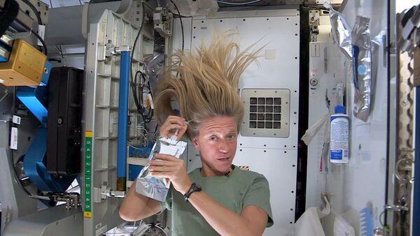 Астронавт Карен Найберг во время мытья головы на борту МКС  - Sputnik Italia