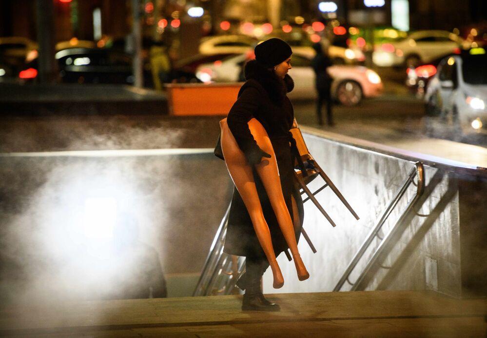 Una donna porta via la parte inferiore di un manichino da un sottopassaggio a Mosca.