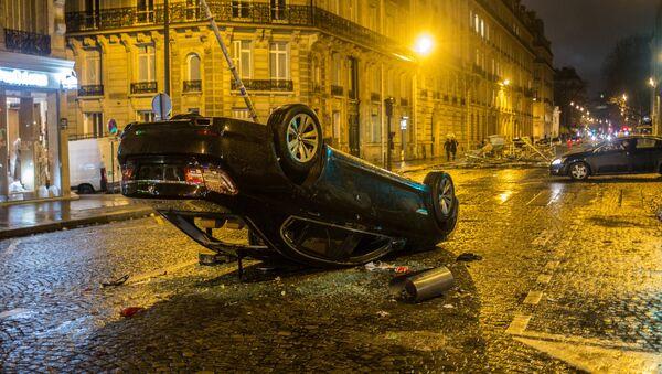 Automobile ribaltata dopo le proteste dei gilet gialli a Parigi - Sputnik Italia