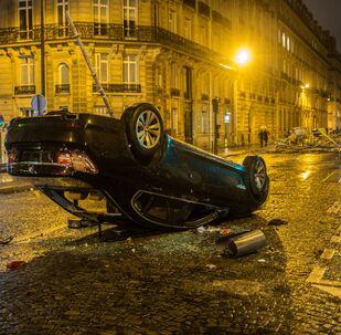 Un'automobile ribaltata dopo le proteste dei gilet gialli a Parigi