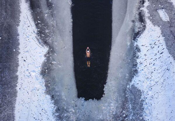 Una persona nuota nel lago parzialmente ghiacciato in Cina - Sputnik Italia