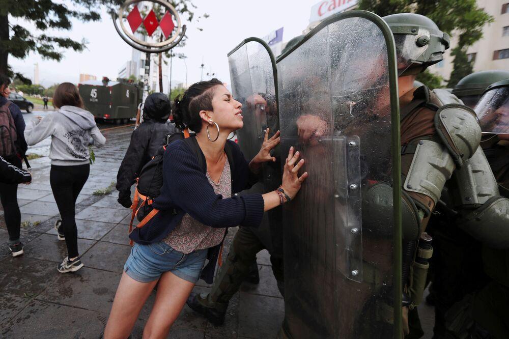 Attivista del popolo Mapuche cerca di remare i poliziotti durante le proteste a Santiago, Cile.