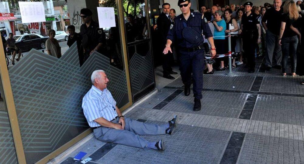 Un uomo, un pensionato greco, piange disperato seduto per terra fuori da una banca di Salonicco.