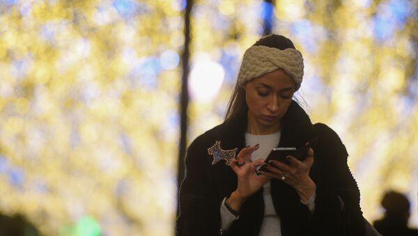 Una ragazza consulta il telefonino nella via Nikolskaya di Mosca, illuminata a festa - Sputnik Italia
