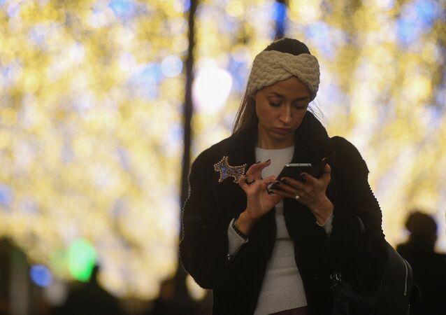 Una ragazza consulta il telefonino nella via Nikolskaya di Mosca, illuminata a festa