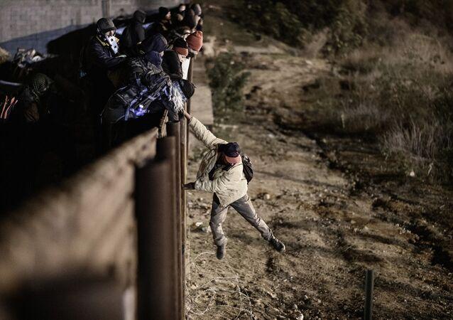 Migranti oltrepassano le barriere al confine tra San Diego e Tijuana