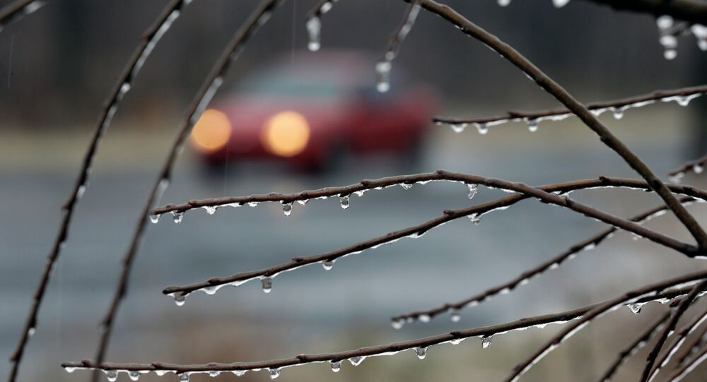 A car drives slowly in the rain on an icy rural road Sunday, Jan. 18, 2015, near Newtown, Pa.