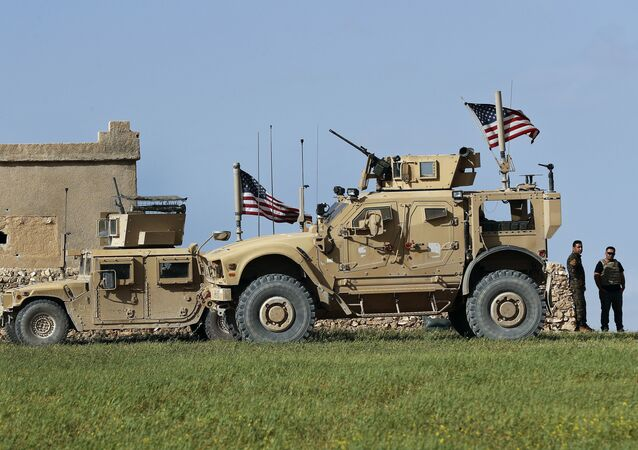 In this picture taken on Thursday, March 29, 2018, a fighter, second from right, of U.S-backed Syrian Manbij Military Council stands next to U.S. humvee at a U.S. troop's outpost on a road leading to the tense front line between Syrian Manbij Military Council fighters and Turkish-backed fighters, at Halawanji village, north of Manbij town, Syria