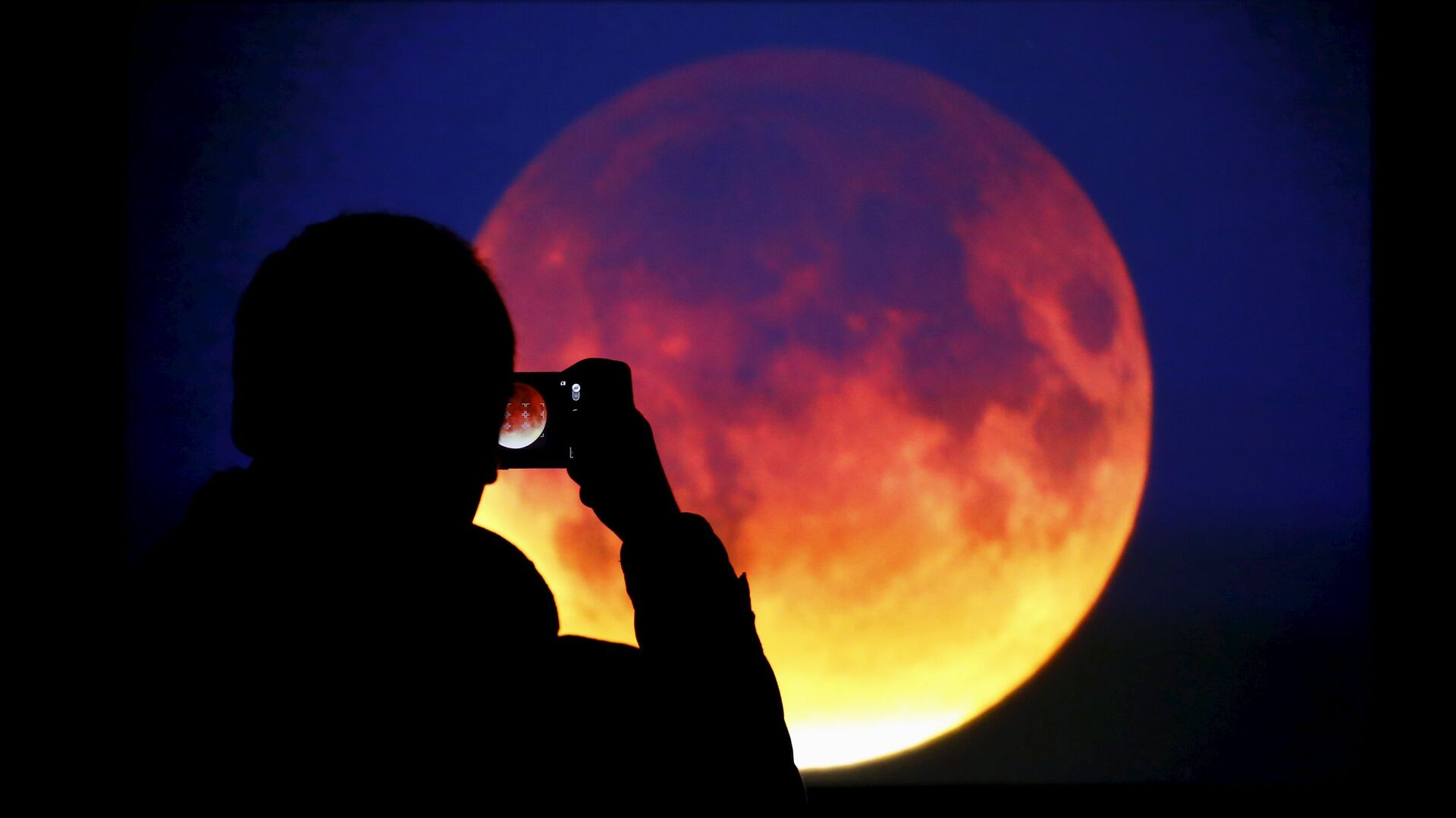A man takes picture of the screen displaying the moon, appearing in a dim red colour, which is covered by the Earth's shadow during a total lunar eclipse in Warsaw, Poland September 28, 2015 - Sputnik Italia, 1920, 25.05.2021