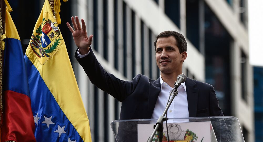 Venezuela's National Assembly head Juan Guaido waves to the crowd during a mass opposition rally against leader Nicolas Maduro in which he declared himself the country's acting president, on the anniversary of a 1958 uprising that overthrew military dictatorship, in Caracas on January 23, 2019.
