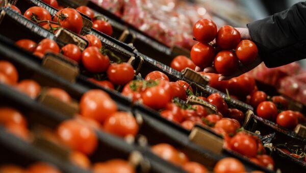 Посетитель выбирает помидоры в гипермаркете Лента в Великом Новгороде - Sputnik Italia