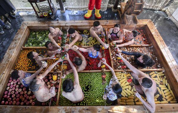 Gli ospiti di un albergo a Hangzhou passano il tempo nella piscina riempita di frutta e verdura alla vigiglia del Capodanno cinese. - Sputnik Italia