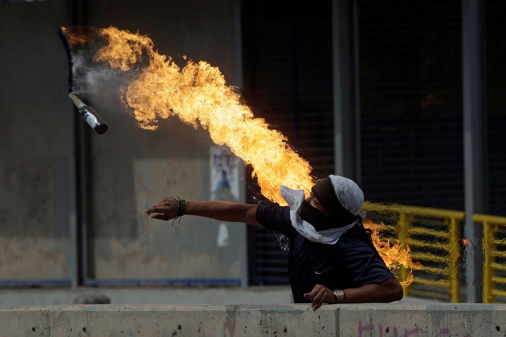 Un ribelle getta una bottiglia con la miscela incendiaria durante le proteste contro il presidente dell'Honduras Juan Orlando Hernandez.