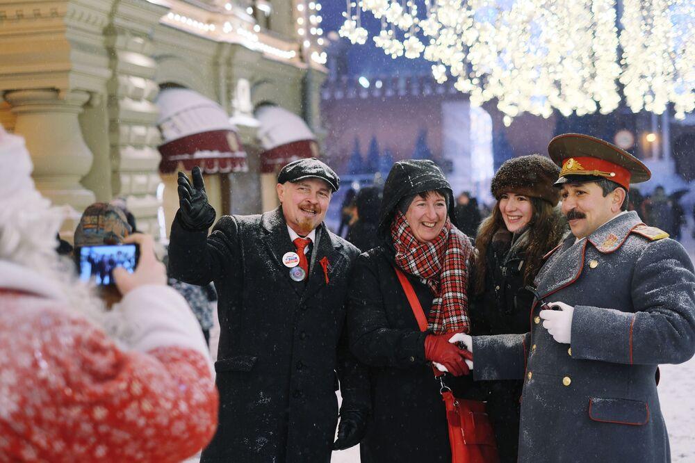 Turisti si fanno le foto con gli uomini vestiti da Lenin e Stalin a Mosca.