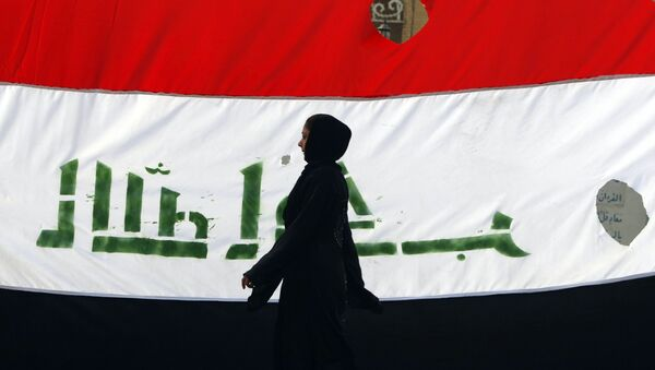 An Iraqi woman walks her national flag during a celebration marking the the departure of US troops from Iraq in Baghdad's Adhamiyah neighbourhood. File photo - Sputnik Italia