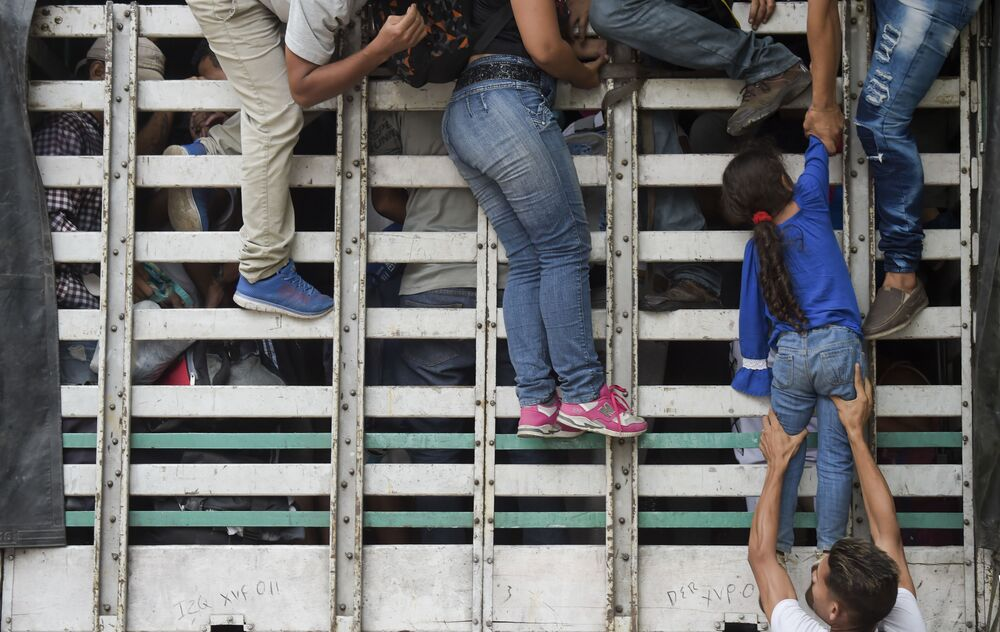 Migranti venezuelani si arrampicano su un furgone durante il tragitto da Cucuta a Pamplona, Colombia.
