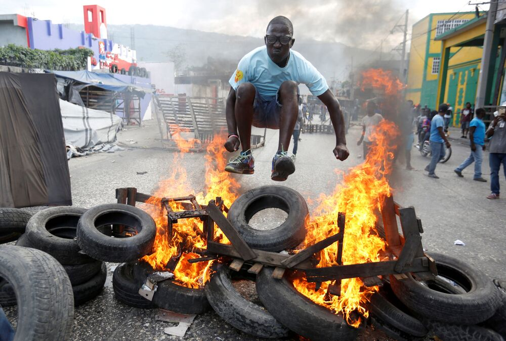 Un manifestante salta oltre una barricata durante una protesta contro il governo nelle strade di Port-au-Prince, Haiti.
