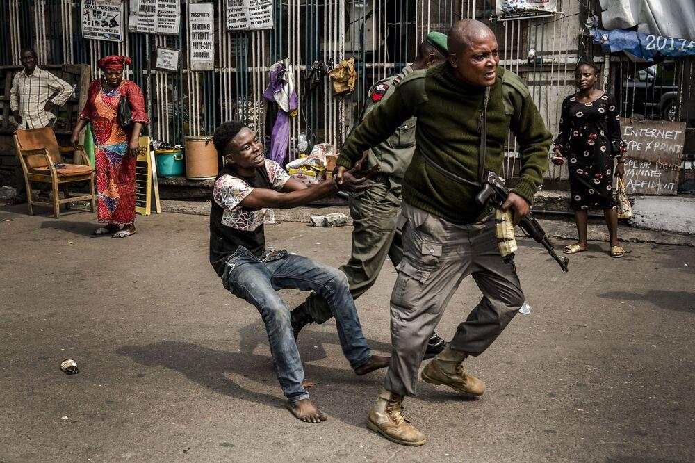 Un poliziotto ferma un ladro in piazza Tafawa Balewa a Lagos, Nigeria.