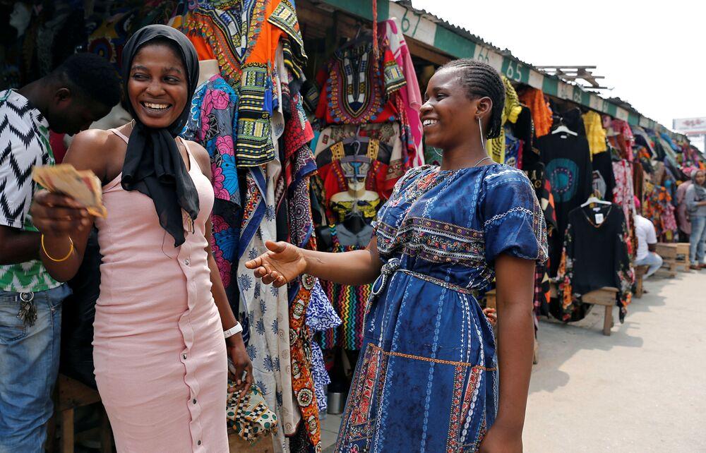 Venditrici si scambiano denaro a Marina, capitale commericale di Lagos, Nigeria.
