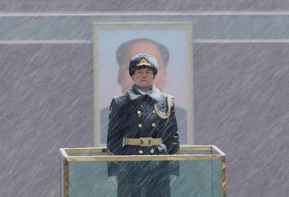 Un militare fa la guardia al ritratto di Mao Zedong durante la nevicata a Pechino.