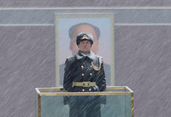 Un militare fa la guardia al ritratto di Mao Zedong durante la nevicata a Pechino. - Sputnik Italia