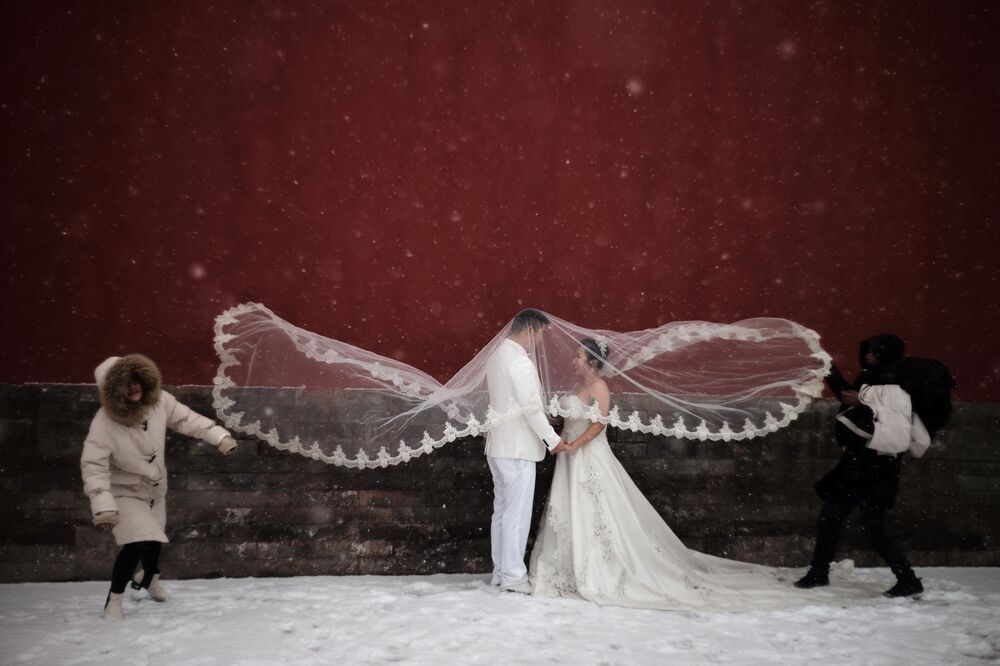 Una coppia posa per le foto di matrimonio durante la nevicata a Pechino.